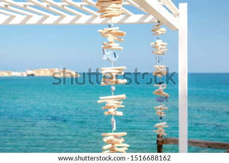 Traditional Greek decoration made of blue wooden fish and sticks suspended on a pergola against the background of a calm sea as a symbol of relaxation and serenity.