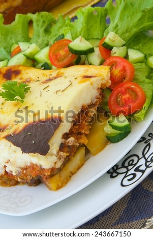 Traditional Greek dish - moussaka - aubergines and potatoes based dish. Served with fresh salad leaves,cherry tomatoes and cucumbers. Glass mold with entire dish is in the background.