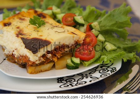 Traditional Greek dish with minced meat - moussaka. Served with fresh vegetables.