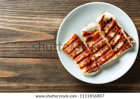 Traditional Greek Grilled Hallumi Cheese on white plate on wooden background. Top view, place for text