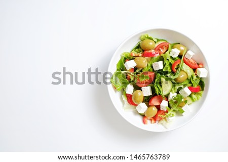 Traditional greek salad with fresh ingredients, feta cheese, olives, red tomatoes, cucumbers and greens in ceramic bowl, isolated on white background. Top view, close up, copy space.