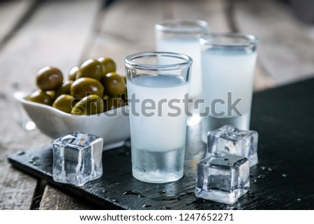Traditional greek vodka - ouzo in shot glasses on rustic wood background