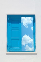 Traditional greek window against a white wall and the cloudy sky and sun