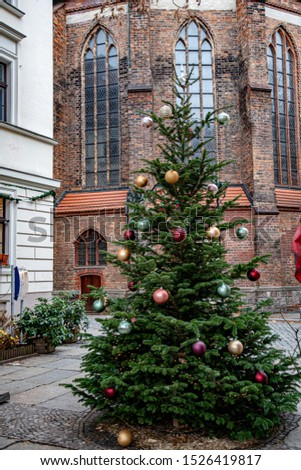 Traditional green spruce Christmas tree decorated with colorful shiny balls and Christmas ornaments on background of old Gothic building brick wall with arch windows. New Year celebration in Europe. #1526419817