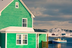Traditional green wooden house at Durrell Harbour of outport fishing town of Twillingate at wintertime, Newfoundland, NL, Canada
