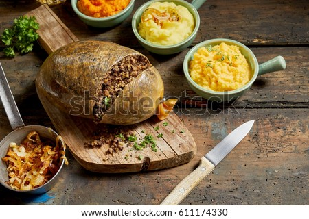 Traditional haggis meal for Robert Burns Supper, a Scottish tradition with cooked sliced haggis, neeps, tatties, onion and carrot on a rustic table