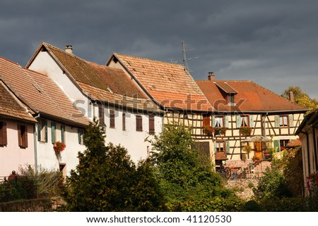 Traditional Half-Timbered Architecture in the Village of Bergheim, Alsace, France. Dramatic Storm Clouds in the Background.