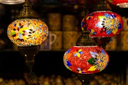 Traditional handmade multicolor Turkish, Moroccan, Arabian lamps hanging with nice blurred background. Mosaic style and colored glass lantern. Suitable for Ramadan Kareem greeting.