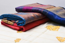 Traditional handmade white, red/pink, blue Indian silk  sari /saree with golden details,  woman use to wear on Onam festival, Vishu, wedding in Kerala India. Close up of stack of multi-colored saree.