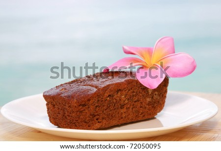 traditional hawaiian banana bread with a hot pink plumeria flower on a white plate outside with the pacific ocean out of focus in the background on the island of maui hawaii