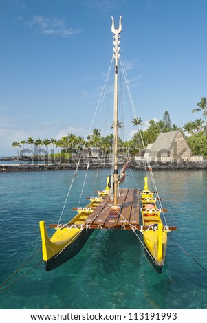 Traditional Hawaiian outrigger canoe lit by the early morning sun floating in a clear ocean water.
