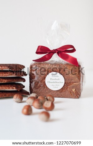 Traditional hazelnut artisan glutenfree Nürnberger Elisenlebkuchen (Elisen Gingerbread) in foil packaging and red bow tie with label saying 'finest Hazelnut Elisen Gingerbread' from Nuremberg, Franconia, Germany on white.