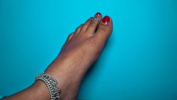 Traditional Hindu woman bride wearing paajeb (Anklets) in India. Female foot with Nail polish isolated on blue background