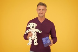 Traditional holidays. Nice gift. From sincere heart. Man celebrate valentines day. Romantic gift. Mature guy gift box yellow background. Vet shop. Man with dog plush toy. Animals care concept.