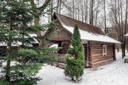 Traditional home under snow at Shrovetide (Pancake week) festival with outdoor snow activities including: armwrestling, bag fighting, cubes moving at Dudutki, Belarus.