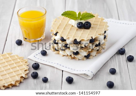 Traditional homemade fresh baked waffles served with blueberries and whipped cream. Dessert and fresh ingredients composition.