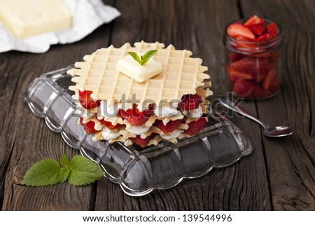 Traditional homemade fresh baked waffles served with strawberries and whipped cream. Dessert and fresh ingredients composition.