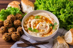 Traditional homemade hummus, falafel and chickpea served with salad and pita and spices on wooden table. Jewish Cuisine. Top view