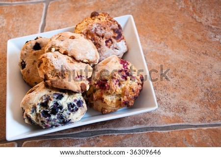 Traditional homemade Raspberry and Blueberry Scones set on stone tiles.