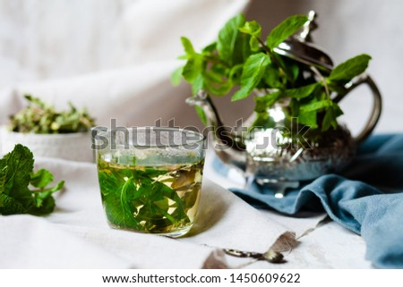 Traditional hot mint moroccan tea served in a transparent cup. Metal teapot with fresh mint on the background. Dry leaves and vintage spoon as decor. Gentle herbal detox, natural depressant #1450609622