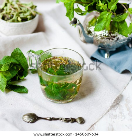 Traditional hot mint moroccan tea served in a transparent cup. Metal teapot with fresh mint on the background. Dry leaves and vintage spoon as decor. Gentle herbal detox, natural depressant #1450609634