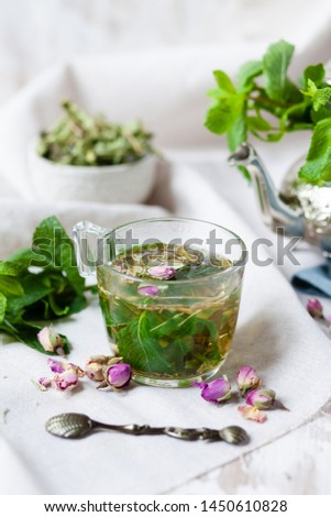 Traditional hot mint moroccan tea served in a transparent cup. Metal teapot with fresh mint on the background. Dry leaves, dry rose flowers and vintage spoon as decor. Gentle detox, natural depressant #1450610828