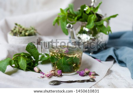 Traditional hot mint moroccan tea served in a transparent cup. Metal teapot with fresh mint on the background. Dry leaves, dry rose flowers and vintage spoon as decor. Gentle detox, natural depressant #1450610831