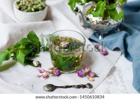 Traditional hot mint moroccan tea served in a transparent cup. Metal teapot with fresh mint on the background. Dry leaves, dry rose flowers and vintage spoon as decor. Gentle detox, natural depressant #1450610834