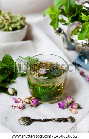 Traditional hot mint moroccan tea served in a transparent cup. Metal teapot with fresh mint on the background. Dry leaves, dry rose flowers and vintage spoon as decor. Gentle detox, natural depressant #1450610852