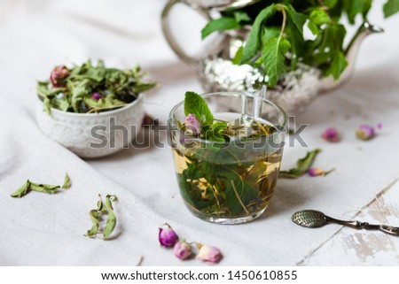 Traditional hot mint moroccan tea served in a transparent cup. Metal teapot with fresh mint on the background. Dry leaves, dry rose flowers and vintage spoon as decor. Gentle detox, natural depressant #1450610855