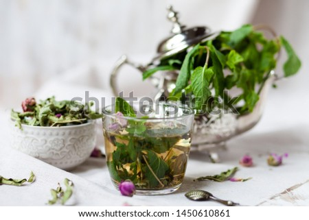 Traditional hot mint moroccan tea served in a transparent cup. Metal teapot with fresh mint on the background. Dry leaves, dry rose flowers and vintage spoon as decor. Gentle detox, natural depressant #1450610861
