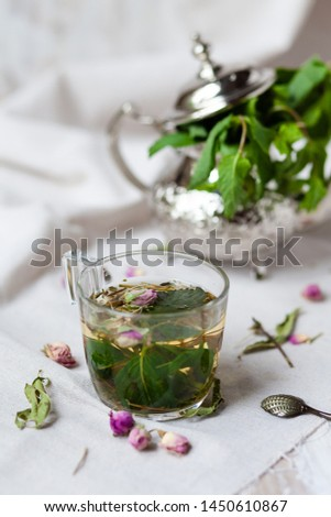 Traditional hot mint moroccan tea served in a transparent cup. Metal teapot with fresh mint on the background. Dry leaves, dry rose flowers and vintage spoon as decor. Gentle detox, natural depressant #1450610867