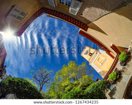Traditional house and church architecture of Eze town, in a sunny day. Fisheye view towards the tower bell of the church and the sky in French Riviera of France