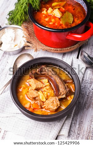 Traditional hungarian dish - bogracs goulash, stewed meat and vegetables in cauldron