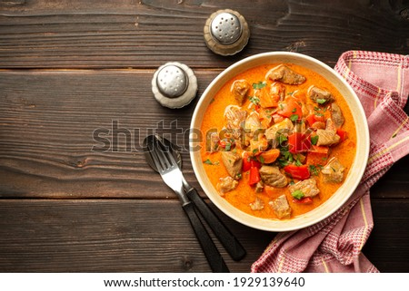 Traditional hungarian paprikash with turkey, bell pepper, carrot, onion, paprika and sour cream in bowl on dark wooden background. Top view, copy space. Foto d'archivio ©