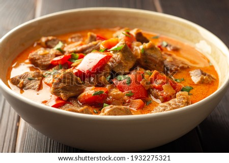 Traditional hungarian paprikash with turkey, bell pepper, carrot, onion, paprika and sour cream in bowl on dark wooden background. Selective focus. Foto d'archivio ©