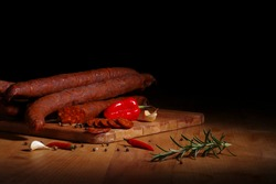 Traditional hungarian smoked sausage with pepper, garlic and rosemary on cutting board