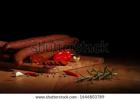 Traditional hungarian smoked sausage with pepper, garlic and rosemary on cutting board Stock fotó ©