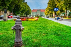 Traditional hydrant with gryphon head from Stettin city emblem, blurred flowerbed and town hall in background. Gryphon in Szczecin emblem since 1360