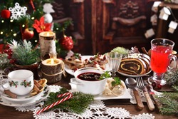 traditional in Poland Christmas Eve dishes with red borscht and dumplings, herring with cranberries and poppy seed roll cake on festive table in rustic style