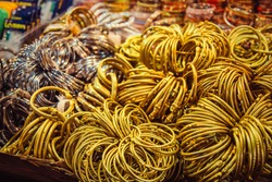 Traditional indian bangles and bracelets at the street market in Rajasthan, India. Jewelry made of gold-plated metal with multicolored stones in the Asian style. Tibetan bracelets