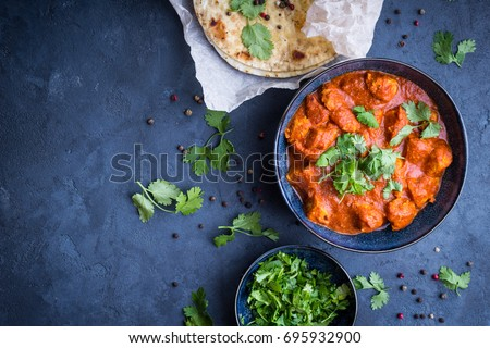 Traditional Indian/British dish chicken tikka masala background. Spicy chicken tikka masala/curry in bowl, indian bread naan, fresh cilantro. Indian style dinner. Space for text. Top view. Indian food