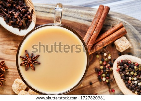 Traditional Indian drink - masala tea with spices. Cardamom, cinnamon, anise, sugar, cloves, pepper on a light wooden background. Flat lay. Clous-up. Foto stock ©