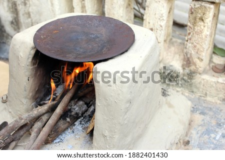 Traditional Indian earthen cooking stove Countryside stove or clay stove with a black colored circular vessel on it, way of making food on open fire in old Indian kitchen