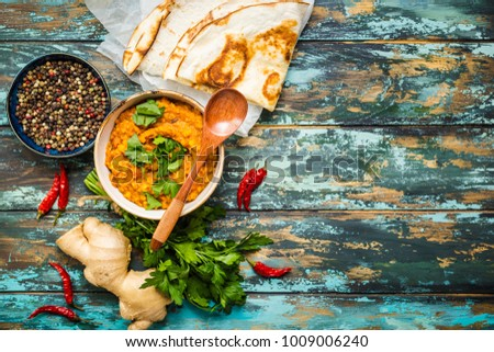 Traditional Indian lentils Dal, naan butter bread. Space for text. Indian Dhal spicy curry in bowl, spices, herbs, rustic wooden background. Top view. Indian food. Authentic Indian dish. Copy space