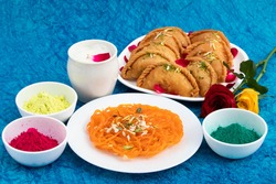 Traditional Indian Sweets Jalebi Ghewar Thandai Bhang Gujia Or Gujiya Mithai And Colorful Gulal Abeer Or Abir For Happy Holi Celebration. Turquoise Background With Copy Space