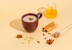 Traditional indian tea. Masala tea in a dark clay cup with ingredients, hard shadows. Cinnamon, cardamom, anise, honey, cloves on a beige background. Close-up. Copy space for text, flat lay.