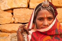 Traditional Indian woman in sari costume covered her face with veil, India