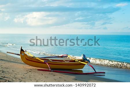 Traditional indonesian fishing boat on Bali ocean beach at sunrise