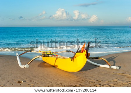 Traditional indonesian fishing boat on Bali ocean beach at sunset
